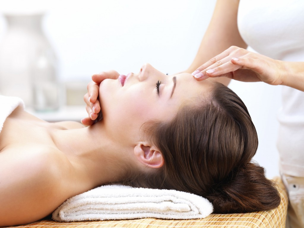 Close up portrait of a young woman with eyes closed receiving facial massage